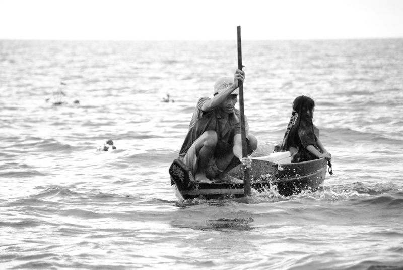 Cambodian fisherman working in the rain